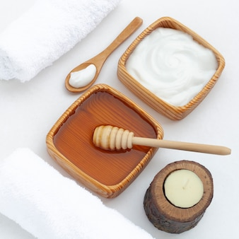 Высокий угол масла для тела и меда на белом фоне