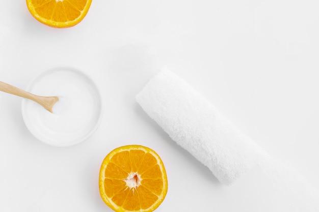 ボディバターと白い背景の上のオレンジのトップビュー
