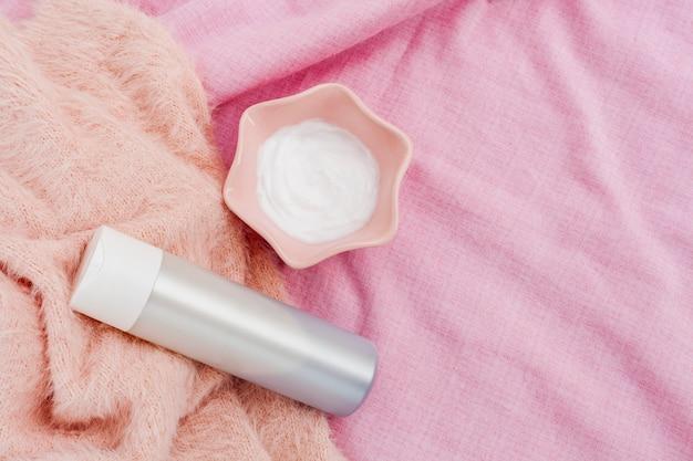 Вид сверху бутылки и масла для тела на розовом фоне