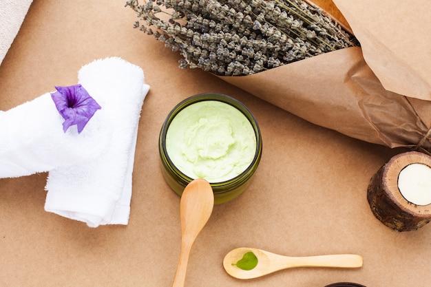 Плоская прокладка масла для тела и лаванды на простом фоне
