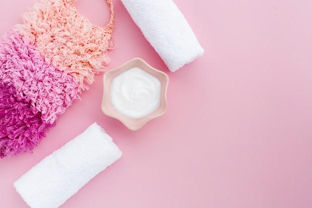 ピンクの背景にボディバターと布のフラットレイアウト