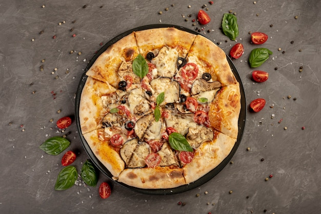 無地の背景にバジルとトマトのピザのフラットレイアウト