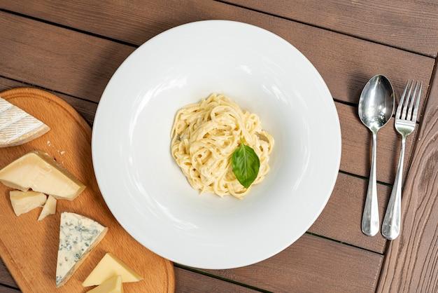 木製のテーブルに美味しいカルボナーラパスタのフラットレイアウト