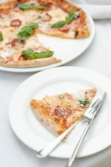 無地の背景にあるプレートにピザのスライスの高角