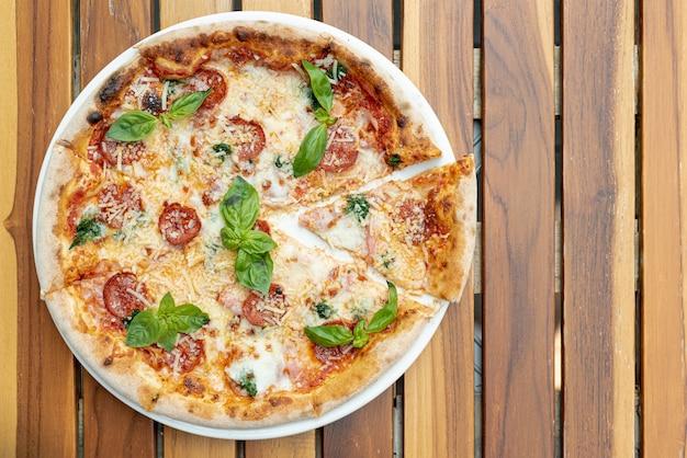 木製テーブルの上のおいしいピザのフラットレイアウト