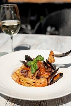 木製のテーブルにスパゲッティとワインの正面図