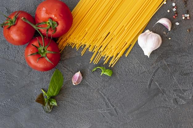 無地の背景にスパゲッティ、トマト、ニンニクのフラットレイアウト