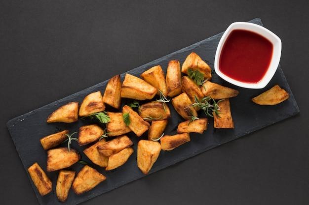 Вид сверху приготовленный картофель с кетчупом в миске