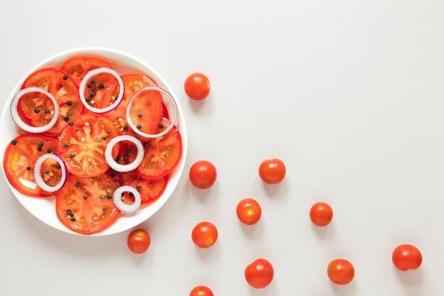 白い背景の上のプレートでトマトと玉ねぎをスライス