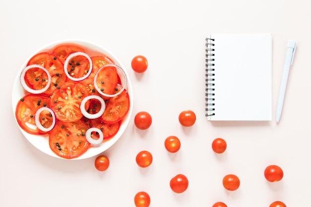 空のノートブックの横にスライスしたトマトと玉ねぎ