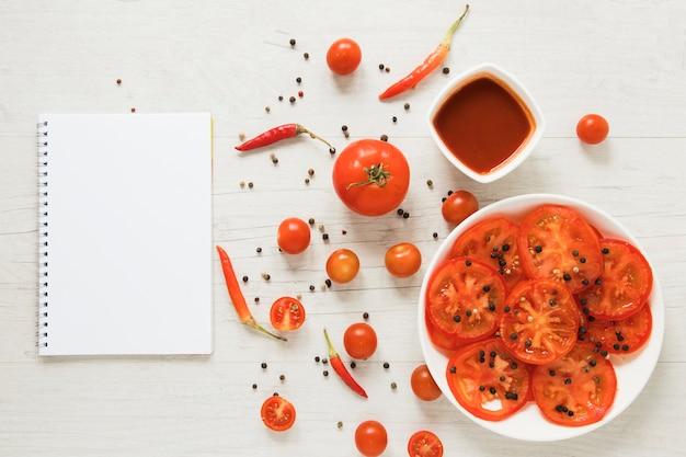 空のノートブックの横にある赤い野菜料理