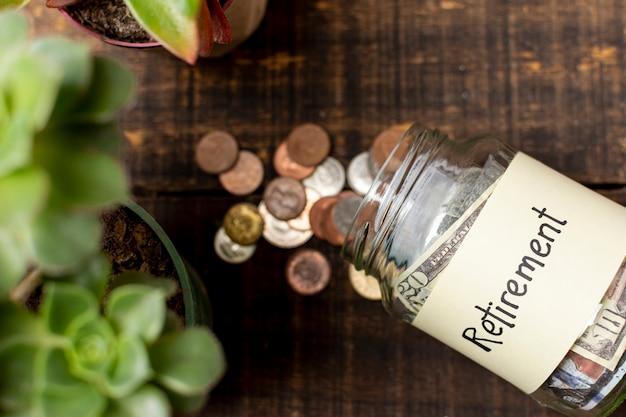 お金のトップビューで満たされた瓶に退職ラベル