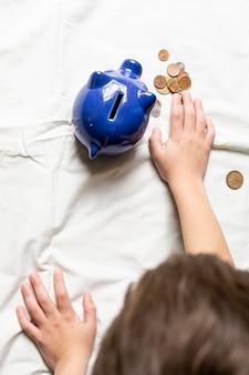 Вид сверху ребенок подсчитывает свои деньги из копилки