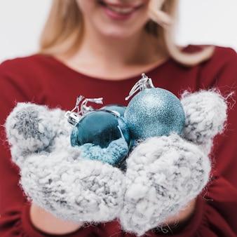 Крупным планом женщина, держащая елочные шары