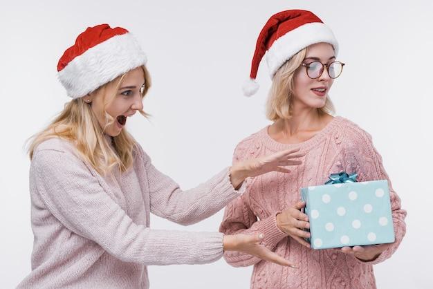 Красивые молодые девушки с подарочной коробкой