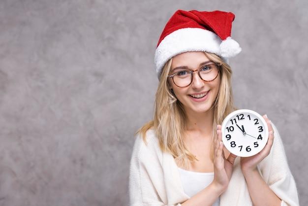 クリスマスの帽子を持つ正面若い女性