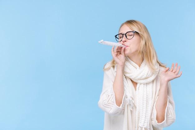 パーティーの送風機を持つ若い女性