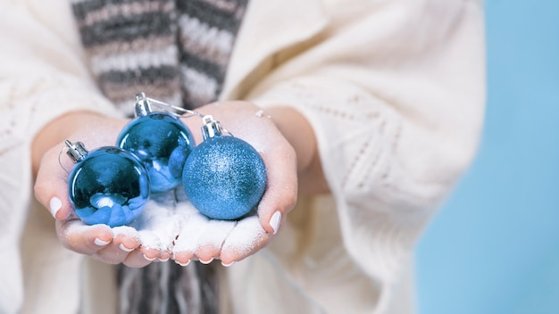クリスマスボールを保持しているクローズアップ手