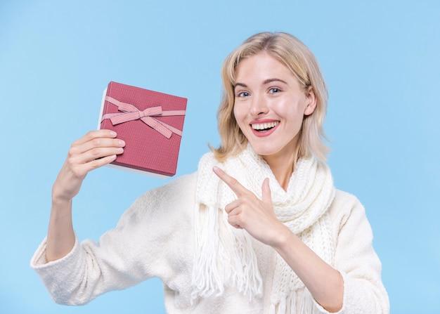 Красивая молодая женщина держит подарок