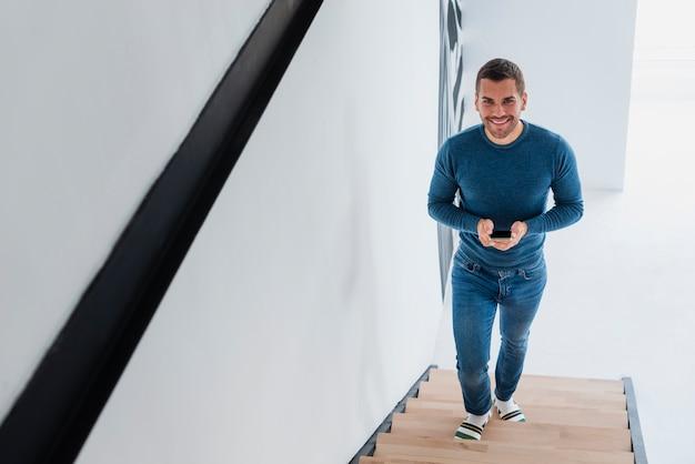 階段を登る手で携帯を持つ男