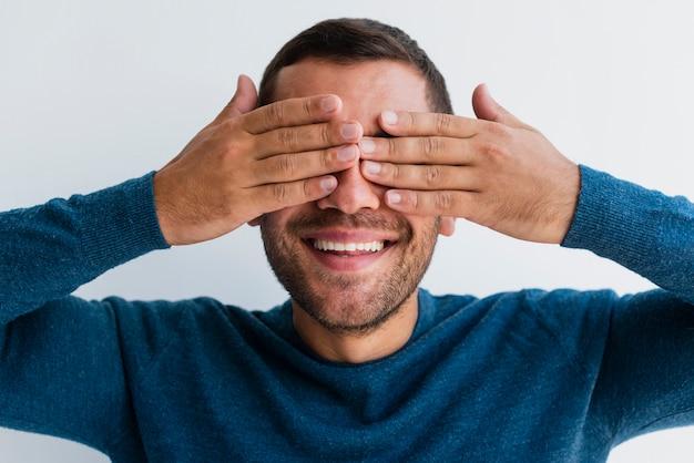 Человек закрывает оба глаза руками