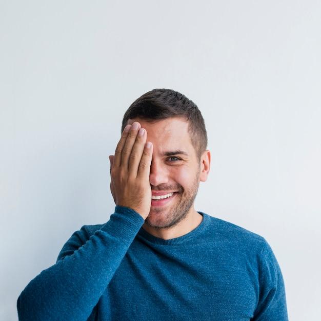 Мужчина улыбается и закрывает половину лица одной рукой