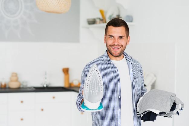 Мужчина показывает на камеру гладить одежду