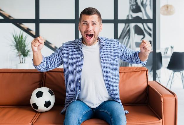 サッカーの試合を見てソファの上の男