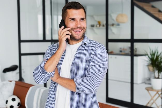 Человек разговаривает по телефону и смотрит в сторону, будучи счастливым