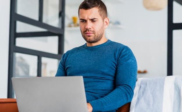 Человек дома работает на ноутбуке