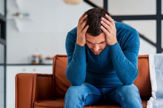 Молодой человек держит голову в руках на диване