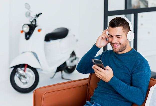 音楽の携帯電話をチェックするヘッドフォンを持つ男