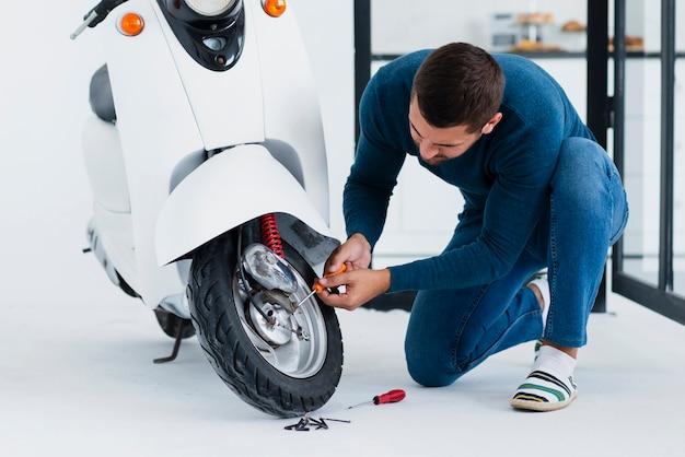 彼のバイクを修理する高角度の男