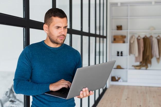 Вид спереди человек с ноутбуком у себя дома
