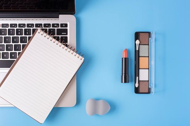 青の背景に化粧品とラップトップのトップビュー