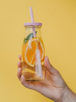 ストローを手に持った天然ジュースの小さな容器