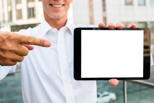 Бизнесмен, указывая на макет планшета