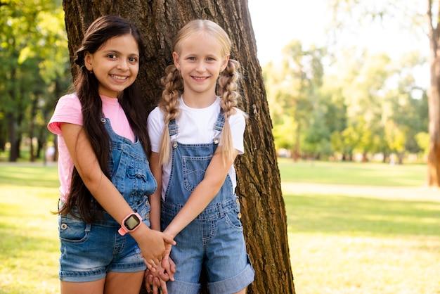 Улыбающиеся молодые подружки держатся за руки