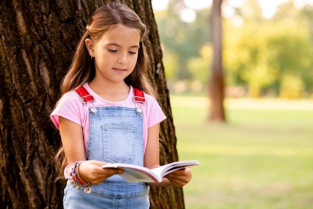 Маленькая девочка в парке читает книгу