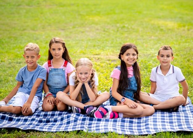 公園の毛布の上に座っている子供たち