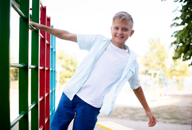 Веселый мальчик цепляется за трубу одной рукой