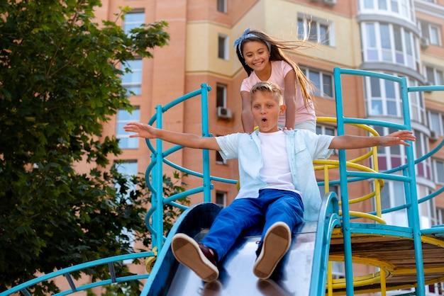 遊び場のスライドで遊ぶ子供たち
