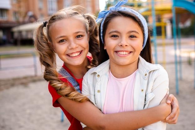 彼女のブルネットのガールフレンドを抱き締めるブロンドの女の子