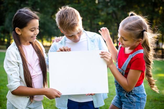 Радостные дети держат чистый лист бумаги