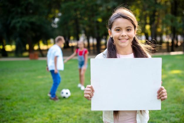Брюнетка девочка держит пустой баннер