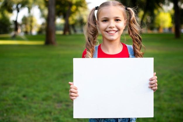 Счастливая девушка держит пустой баннер в руке