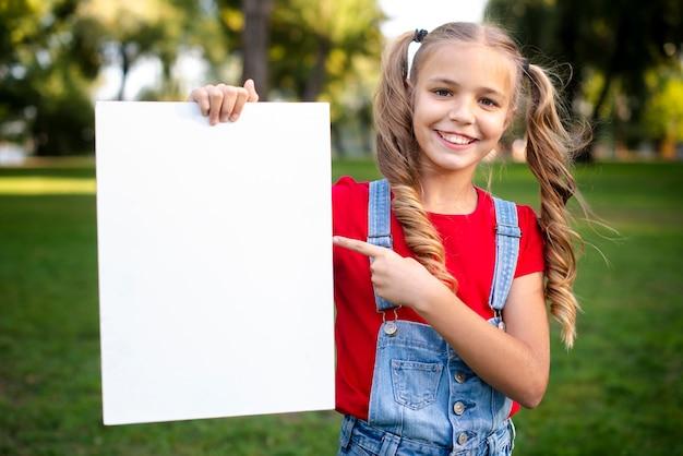 Милая девушка держит пустой баннер в руке