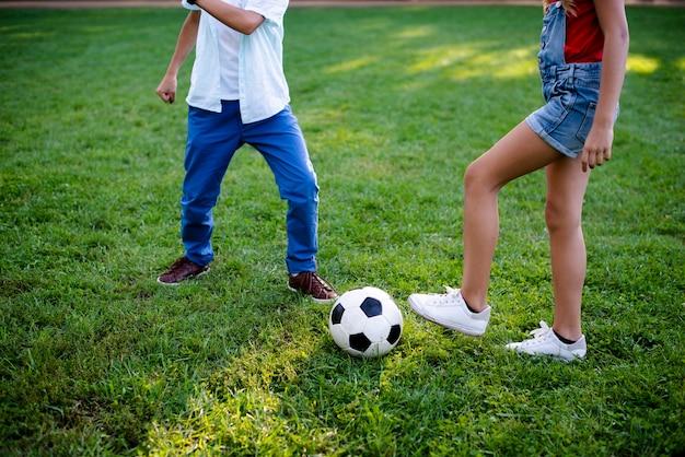 Двое детей играют в футбол на траве