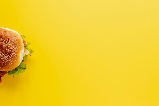 半分のハンバーガーと黄色の背景を持つトップビューフレーム