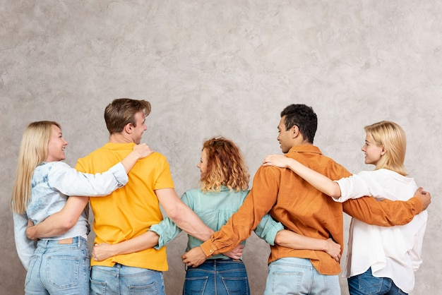 Вид сзади друзья обнимаются и смотрят друг на друга